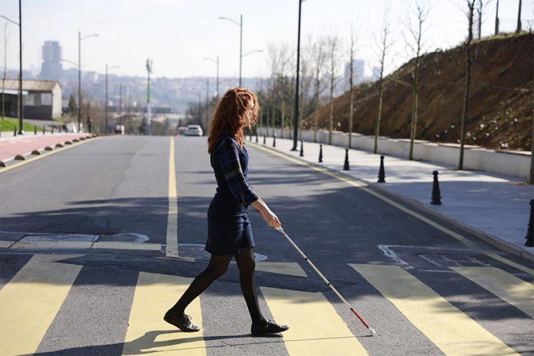 Девојка преминува улица со бел стап.