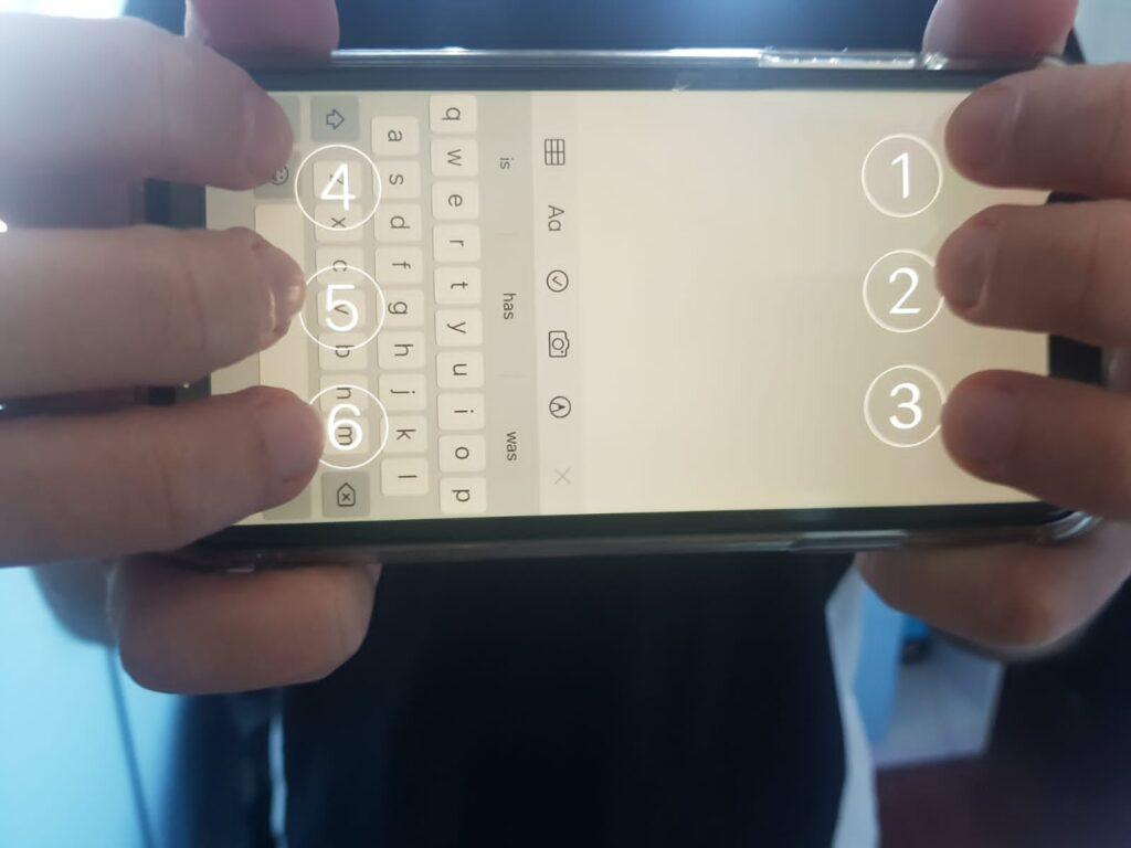 Раце како го држат телефонот во позиција за брајовата тастатура