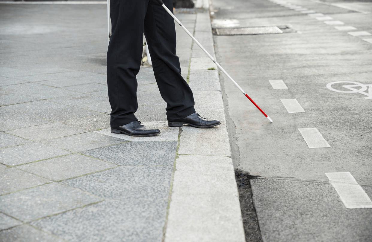 Човек на тротоар ја испитува улицата со бел стап