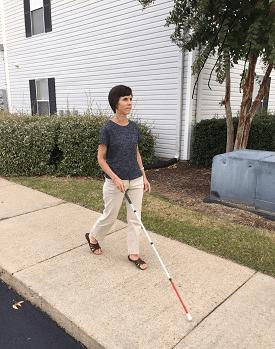 Слепа жена се движи по тротоар со помош на бел стап
