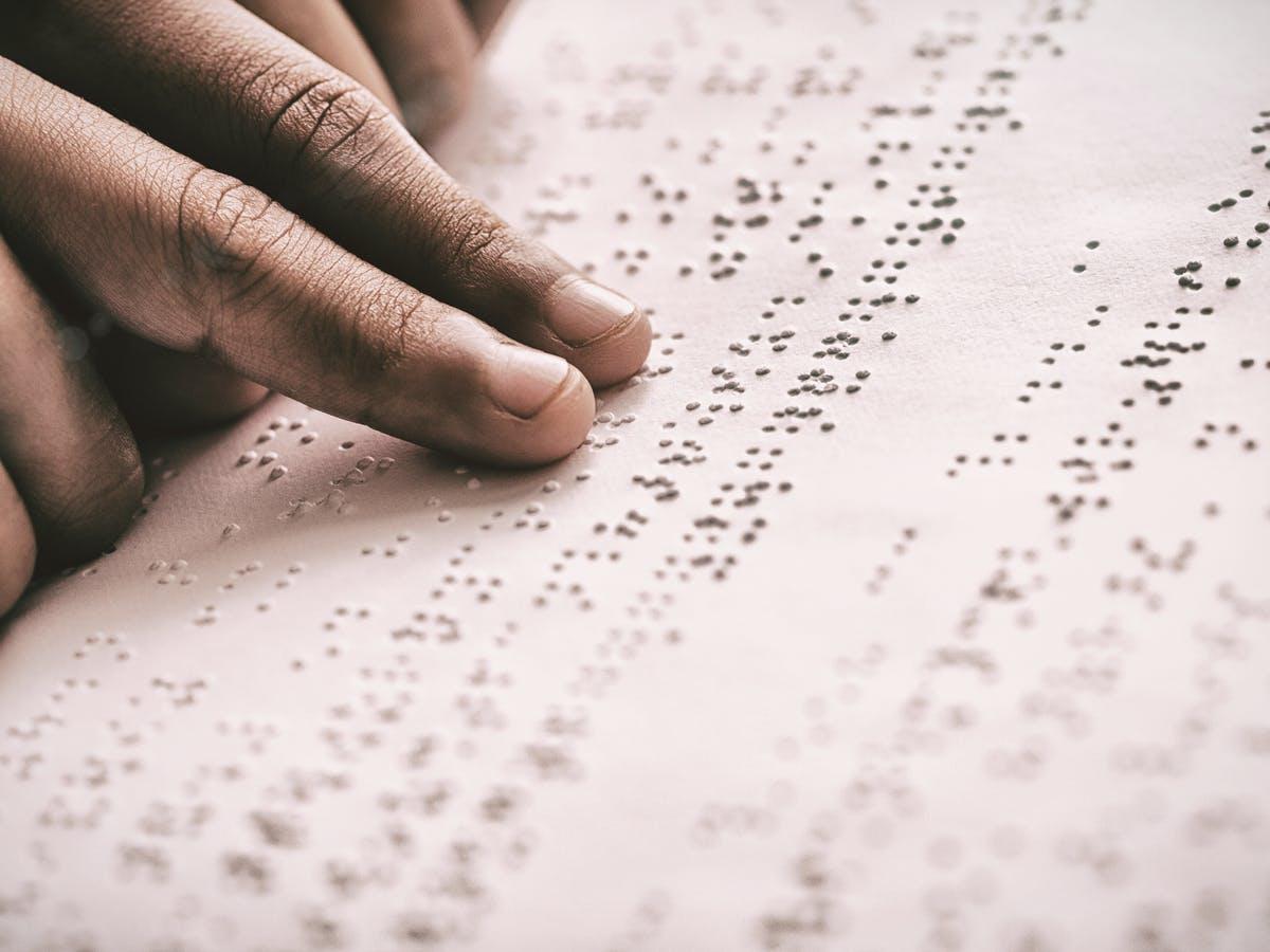 Слика од раце коишто се движат над точките од брајовото писмо