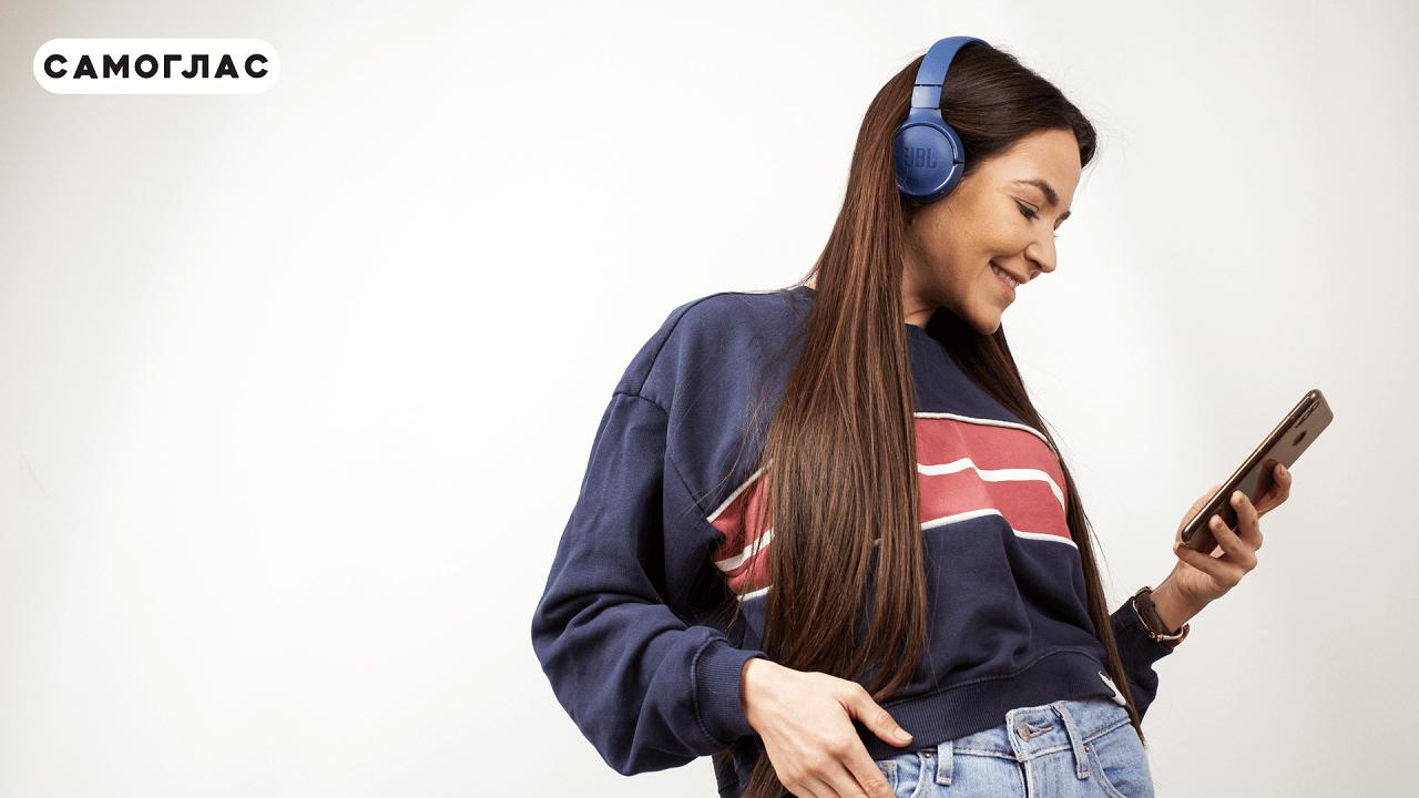 Промотивна слика на Самоглас. На сликата има девојка којашто носи слушалки и слуша аудио книга на телефон.