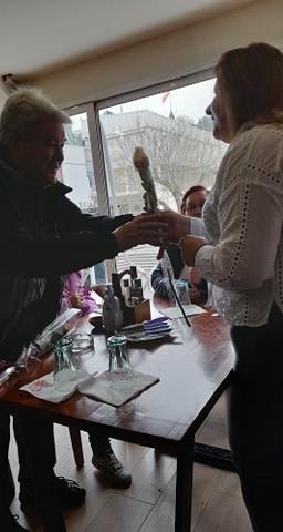 Маж подарува цвеќе на жена во бела кошула