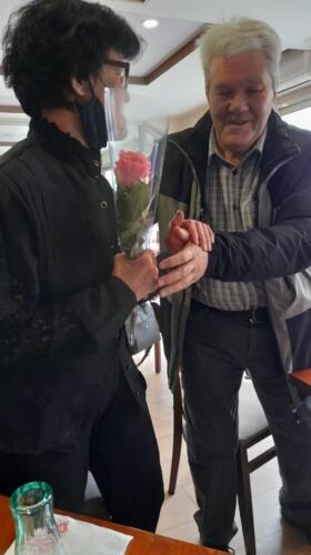 Маж подарува цвеќе на жена во црна кошула